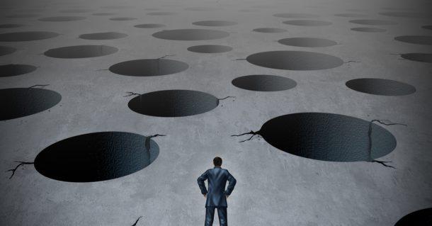 business man looking at pitfalls